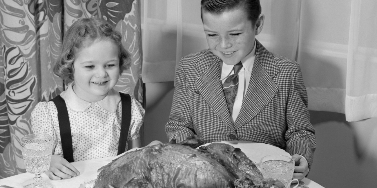 UNITED STATES - Circa 1950s: Boy & Girl Smiling At The Platter With A Roast Turkey On It At The Dining Room Table The Boy Is Wearing A Shirt Tie & Check Jacket The Girl A Jumper Set. (Photo by H. Armstrong Roberts/Retrofile/Getty Images)
